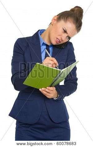 Concerned Business Woman Talking Mobile Phone And Writing In Notepad