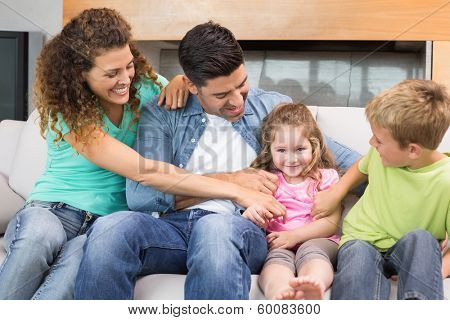 Cute family tickling little girl on the couch at home in living room