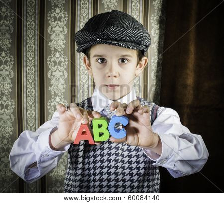 Child In Vintage Clothes Hold Letters A B C