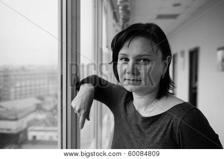 35 year old woman stands in front of the window. Real people series
