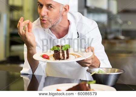 Closeup portrait of a smiling male pastry chef with dessert in the kitchen