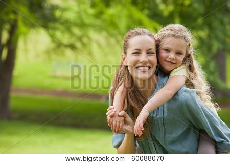 Portrait of a woman carrying young girl at the park