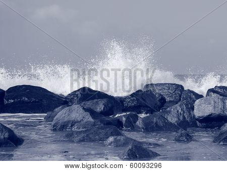 Black Rocks Protecting Coast Against Crashing White Waves