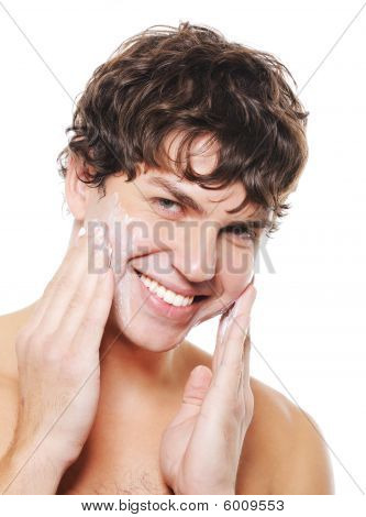 Handsome Smiling Guy  Applying Moisturizing Cosmetic Cream