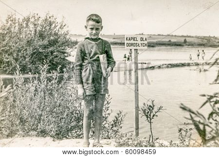 POLAND, CIRCA FORTIES - Vintage photo of little boy at lakeside. The sign says: Swimming only for adults
