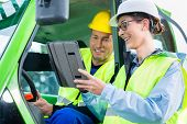 Construction worker in construction machinery discussing with engineer blueprints on pad or tablet c