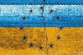 Cracked brick wall as Ukraine flag, symbolize the recent people strike