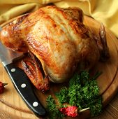 stock photo of christmas meal  - Roasted whole chicken on a cutting board - JPG