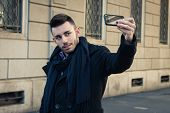 picture of selfie  - Portrait of a handsome young man with scarf taking a selfie - JPG