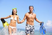 Beach couple having fun in water laughing with snorkeling fins together smiling happy and joyful. Su