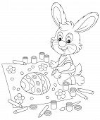 foto of cony  - Easter rabbit drawing a decorated egg and flowers on a big sheet of paper - JPG