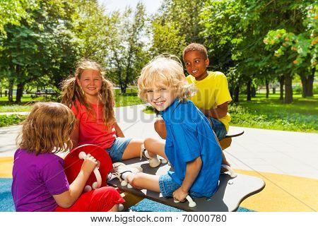 Happy children sitting on playground carousel