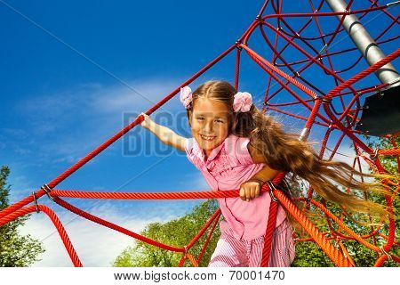 Smiling girl with long hair stands on red rope