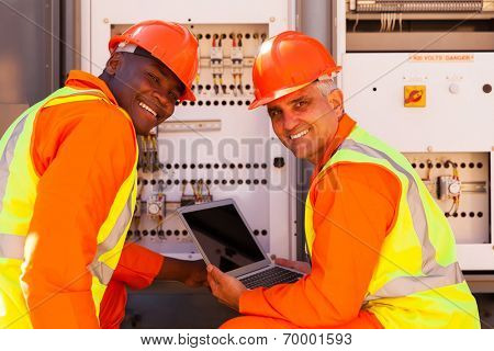 modern electrical co-workers using laptop computer checking transformer
