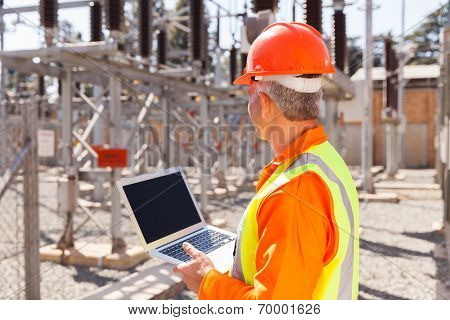 senior technician holding laptop computer in substation