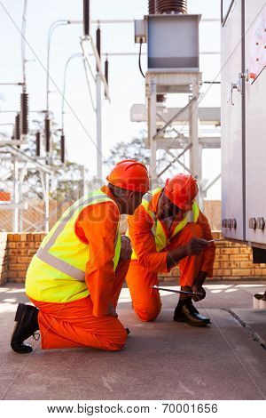 professional power company electrical co-workers in substation
