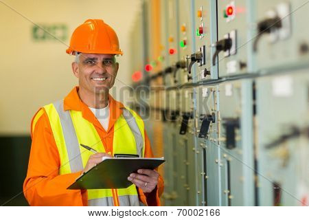 portrait of smiling mature electrician working in control room