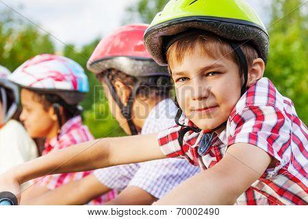 Looking boy in helmet with African guys behind