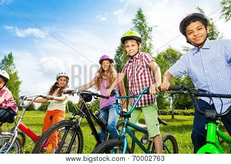 Row of happy children in bike colorful helmets