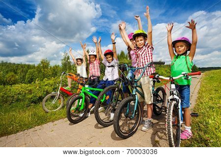 Children with helmets sit on their bikes in a row