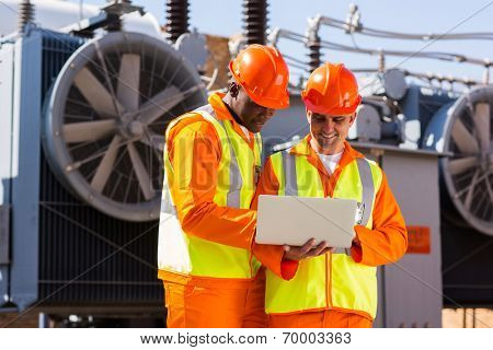 electrical engineers using laptop computer in electric substation