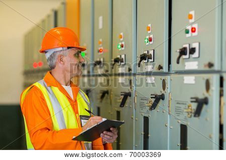 senior technician writing results of measurements in power plant control room