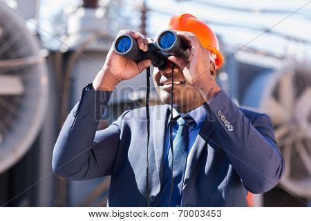 african electrician engineer using binoculars looking at electricity substation