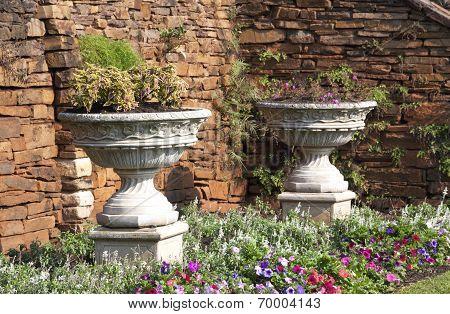 Two Urn Flower Pots In Garden Setting