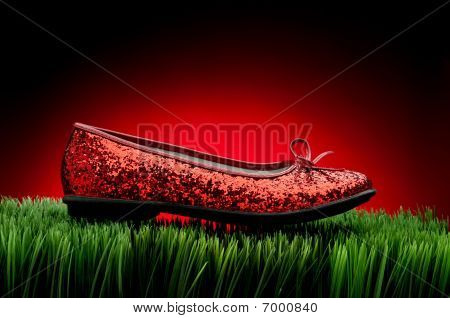 Sequined Red Slipper On Green Grass Against A Fading Red Background