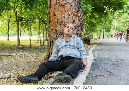 A Fat Asian Guy Sleeping Under The Tree Beside The Street.