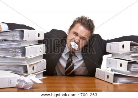 Stressed Business Man Is Frustrated In Office Between Folder Stack