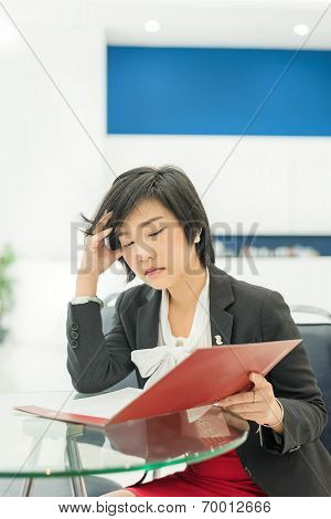 Stress Thai (asian) Businesswoman Is Reading Her Document File In Office