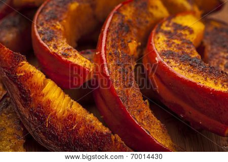 Closeup of freshly roasted pumpkin slices with spices and herbs