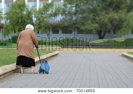 Old woman with bag seen from behind. Grandmother tired.