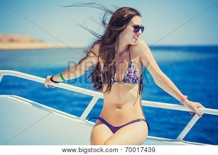 Young woman in bikini enjoying the viewon  yacht