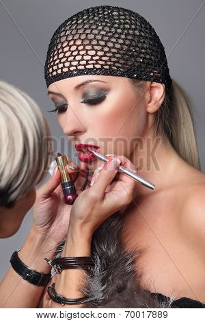 Beauty girl with makeup lip gloss and hairnet. Makeup artist applying lip gloss on face of woman.