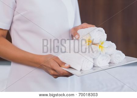 Close up mid section of female masseur holding rolled up towels