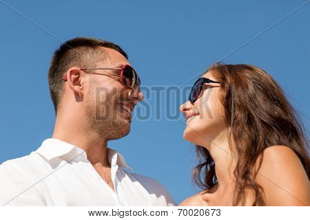 love, travel, tourism, people and friendship concept - smiling couple wearing sunglasses looking at each over blue sky background