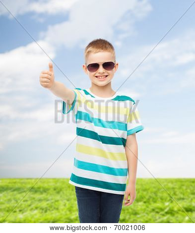 happiness, summer, childhood, gesture and people concept - smiling cute little boy in sunglasses over natural background showing thumbs up