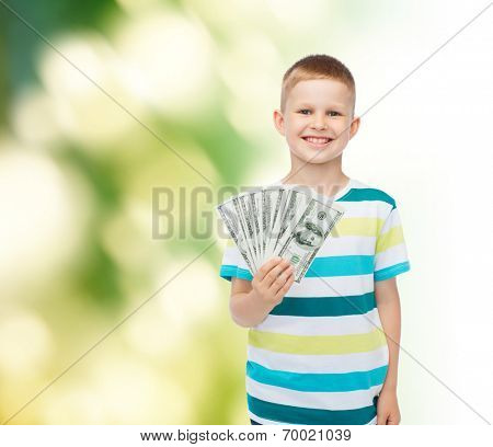 financial, planning, childhood and ecology concept - smiling boy holding dollar cash money in his hand over green background