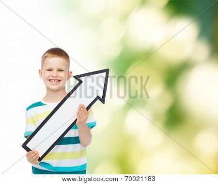 advertising, direction, ecology and childhood concept - smiling little boy with white blank arrow pointing up over green background