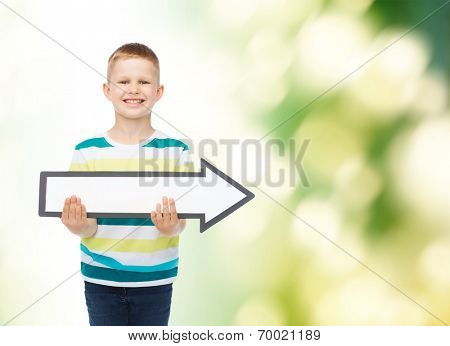 advertising, direction, ecology and childhood concept - smiling little boy with white blank arrow pointing right over green background