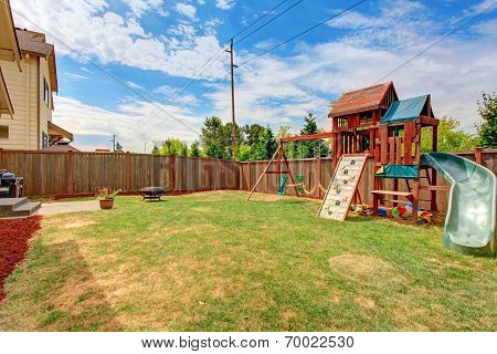 Fenced Backyard With Playground For Kids