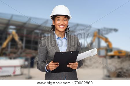 building, developing, construction and architecture concept - smiling woman in white helmet with blueprint and clipboard