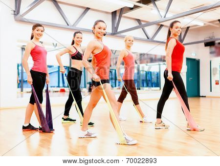fitness, sport, training, gym and lifestyle concept - group of smiling people with instructor working out with rubber bands in the gym