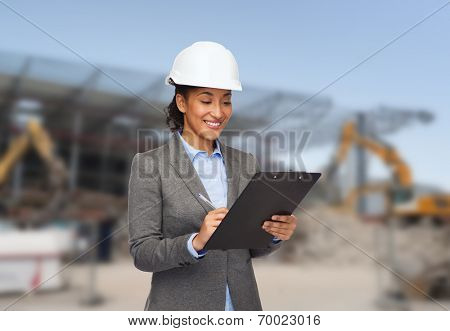 building, developing, construction and architecture concept - smiling african american businesswoman in white helmet with clipboard