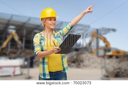 repair, building, construction, maintenance and gesture concept - smiling woman in helmet with clipboard pointing finger