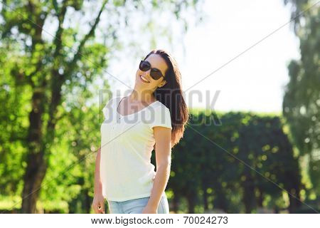 summer, leasure, vacation and people concept - smiling young woman wearing sunglasses standing in park