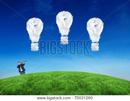 Composite image of businessman looking through telescope against cloud light bulbs