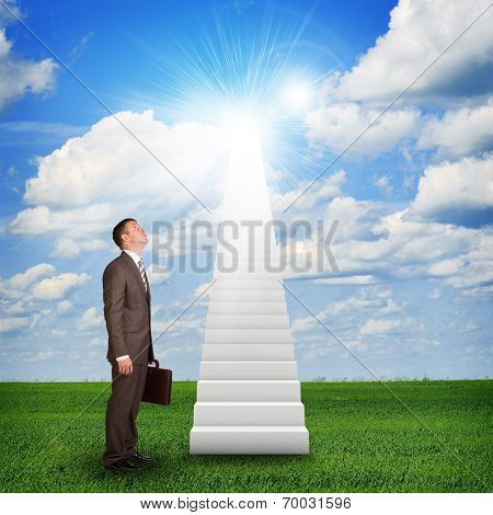 Businessman looking to stairs in sky